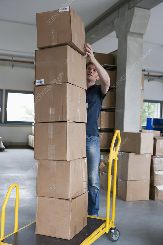 Man stacking cardboard boxes on dolly