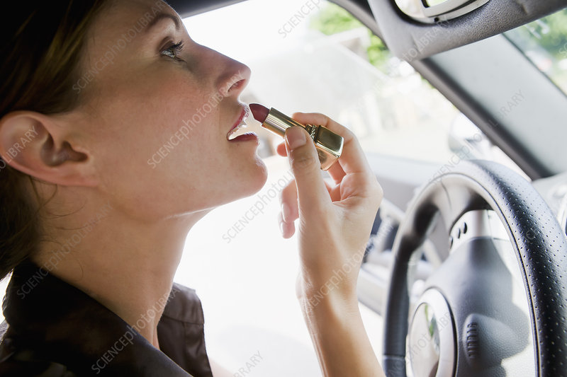 Woman applying lipstick in car mirror