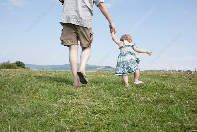 Father walking with daughter in field