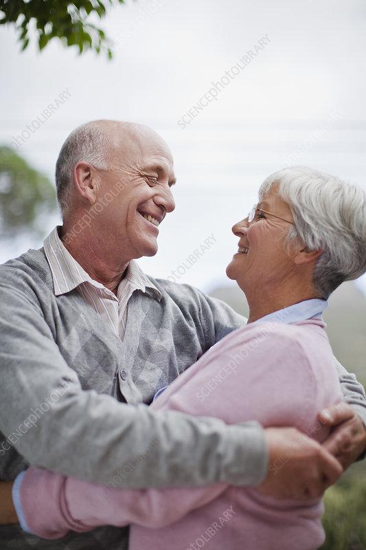Smiling older couple hugging outdoors