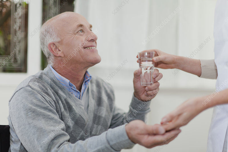Older woman giving husband medication