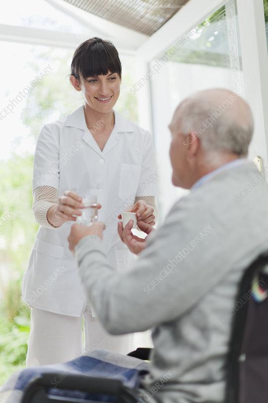 Nurse giving older patient medication