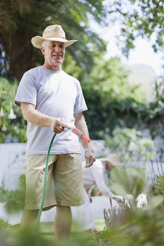 Older man watering plants in backyard