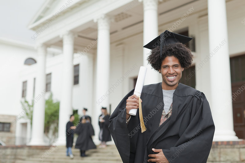 Graduate holding his degree on campus