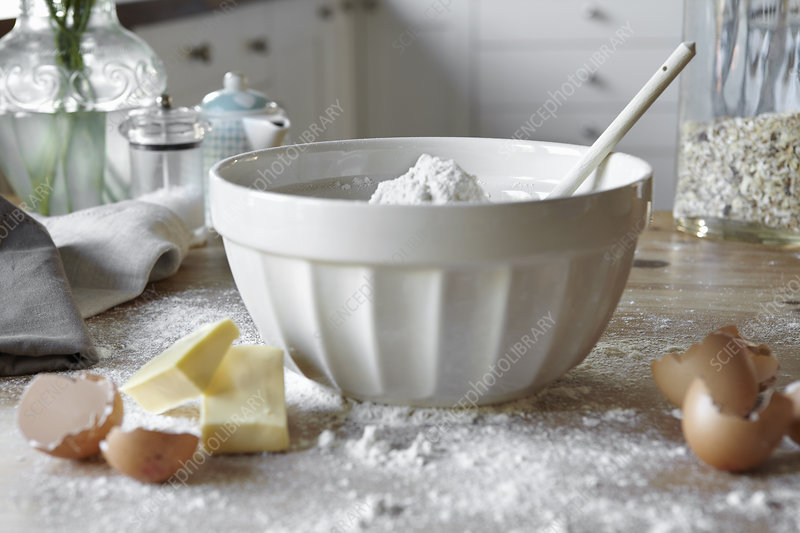 Bowl of mixing dough in messy kitchen