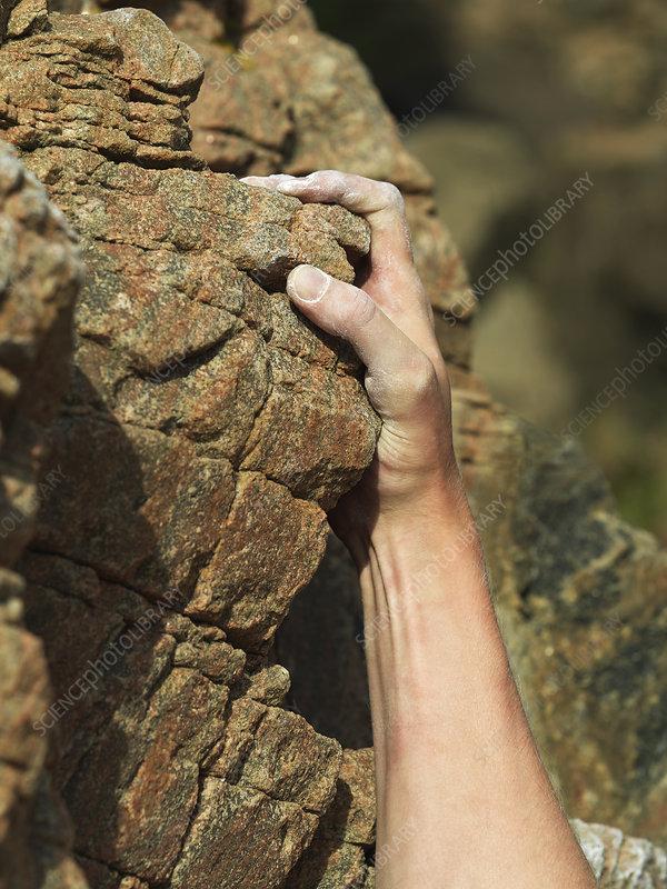 Rock climbers hand on steep rock face