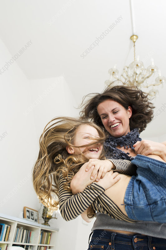 Woman playing with daughter in kitchen