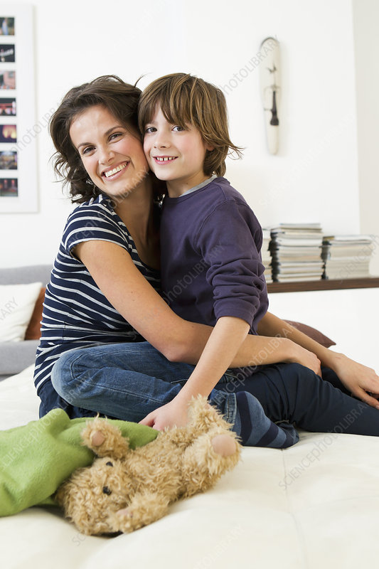 Mother and son relaxing in living room