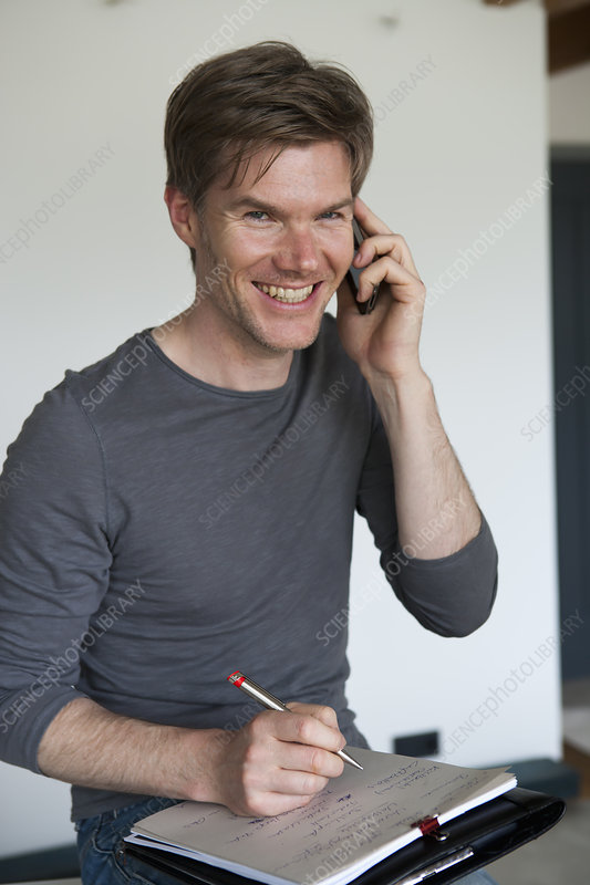 Smiling man on cell phone taking notes