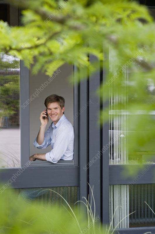 Businessman using cell phone in window