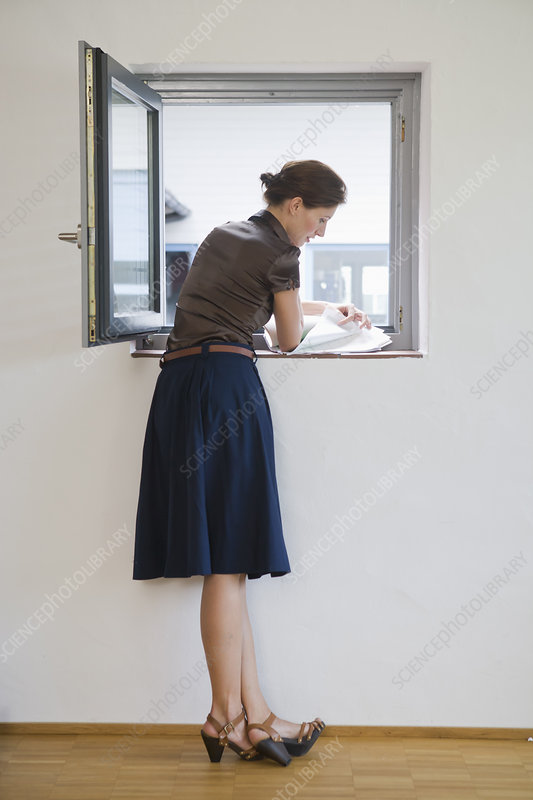 Businesswoman reading papers in window