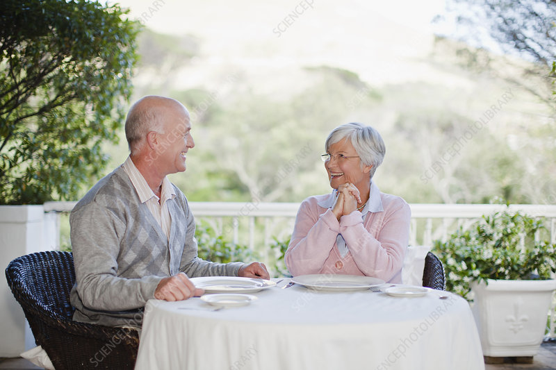 Older couple sitting at table outdoors