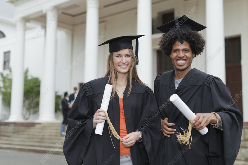 Graduates with their degrees on campus
