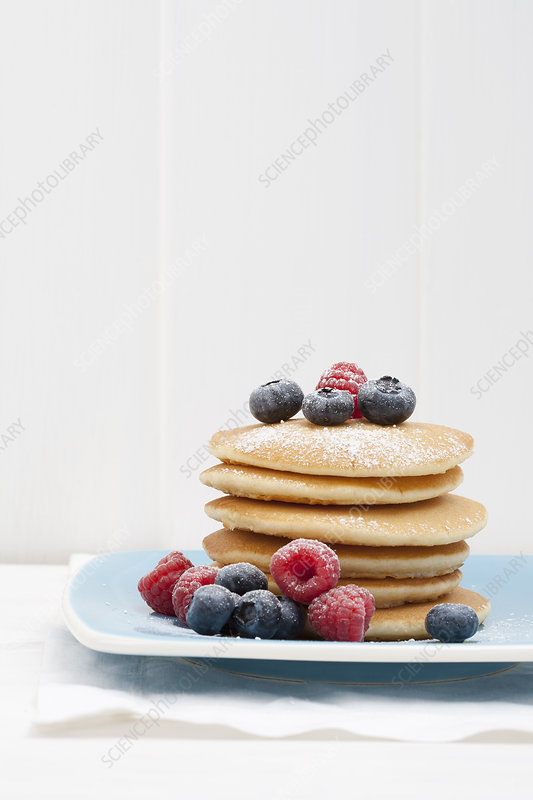 Berries and sugar on stack of pancakes