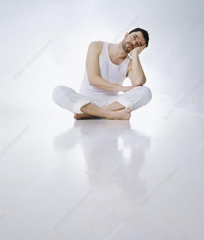 Cross-legged man resting head in hands