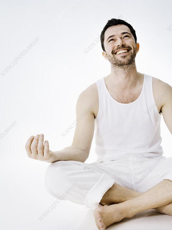Smiling man sitting in meditative pose