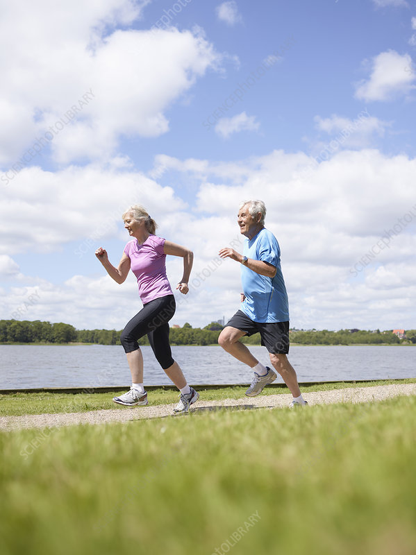 Older couple running together outdoors