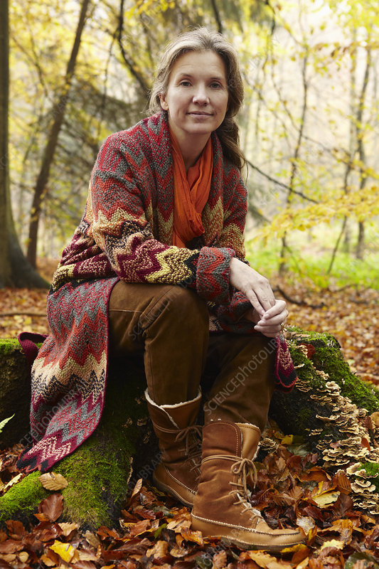 Older woman sitting on stump in forest