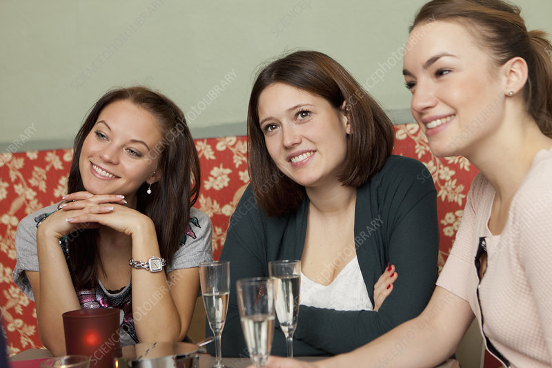 Smiling women having champagne in cafe