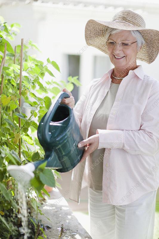 Older woman watering plants in backyard