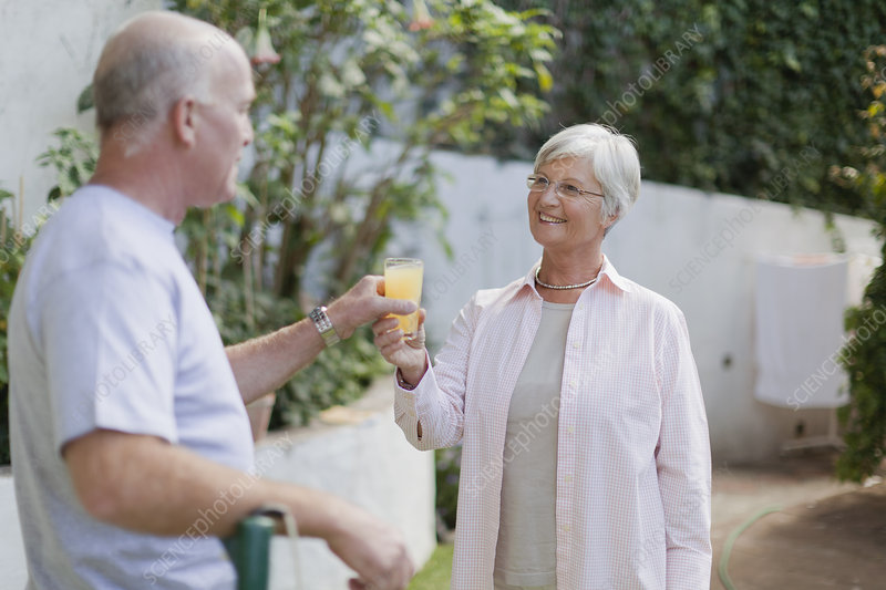 Older couple drinking juice in backyard