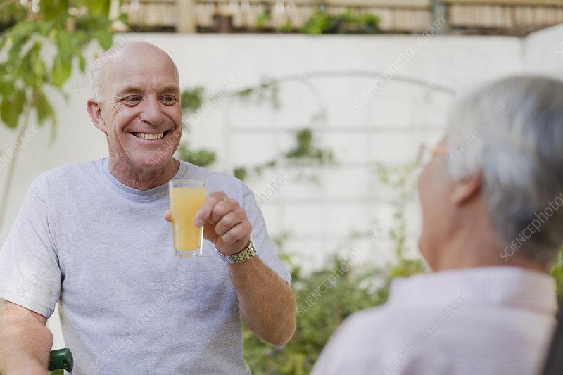 Older couple drinking juice in backyard