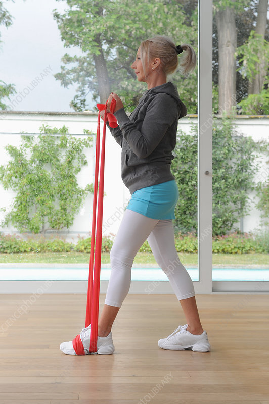 Older woman using exercise band at home