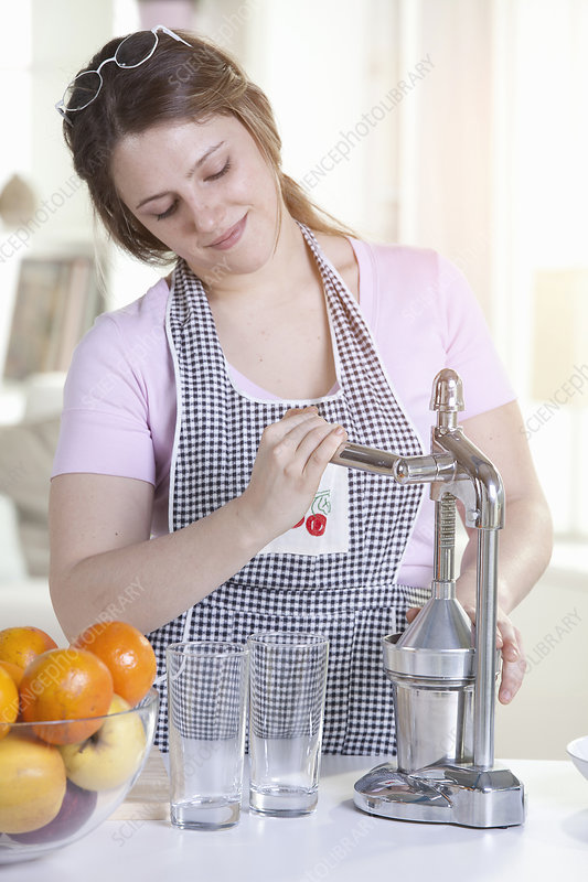 Woman squeezing orange juice in kitchen