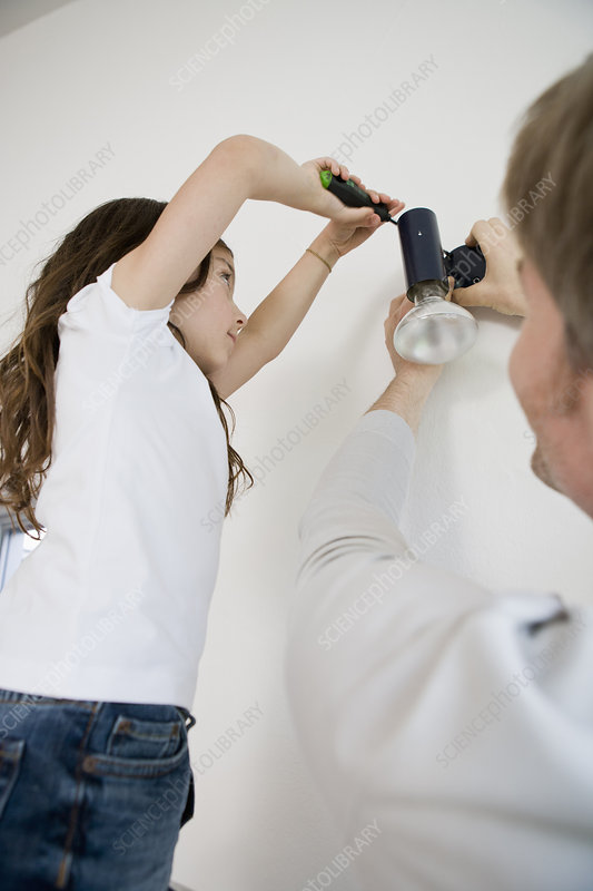 Father and daughter fixing light fixture