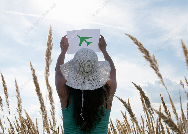 Woman holding picture of airplane in sky