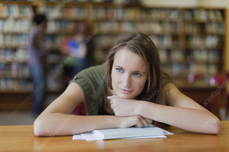 Student resting chin on books in library