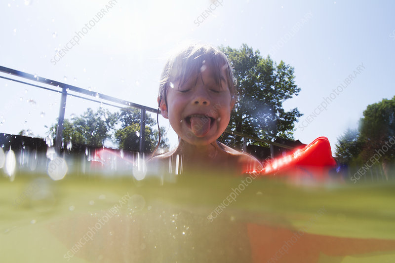 Boy in swimming pool sticking out tongue