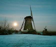 Rural windmill on frozen river