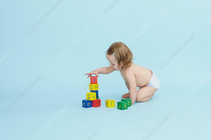Baby girl playing with colored blocks
