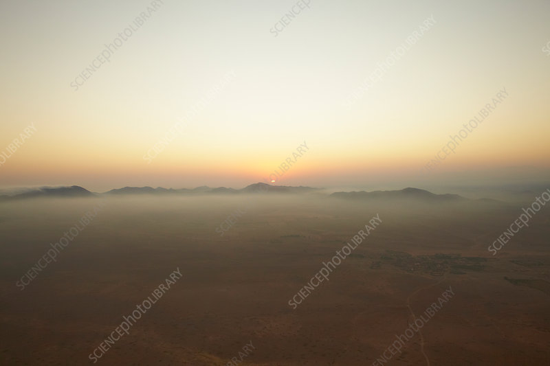 Sun setting over foggy landscape