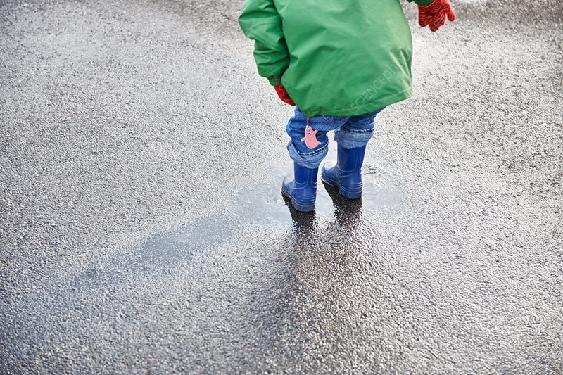 Boy in rain boots playing in puddle