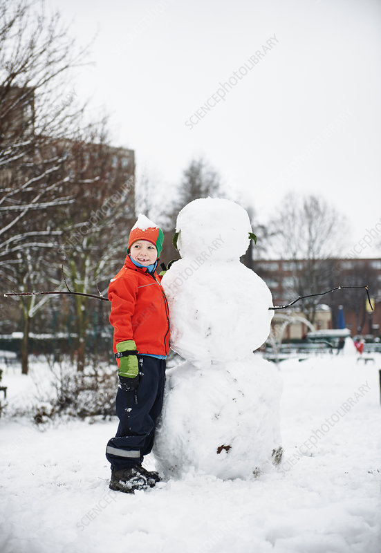 Boy building snowman in park