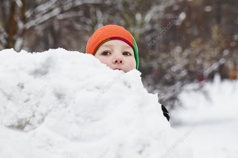 Boy playing in snow in park