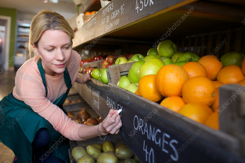 Grocer labelling produce for sale