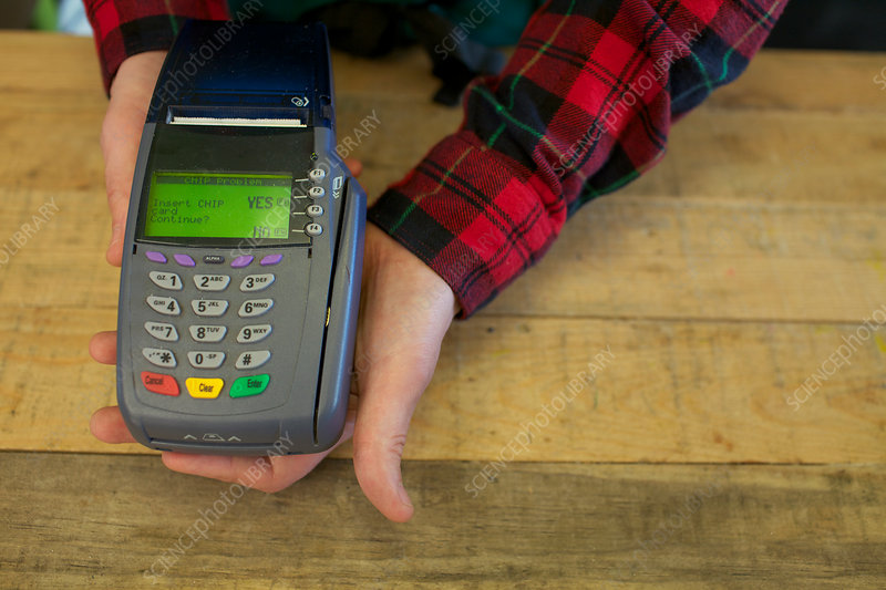 Grocer holding credit card machine