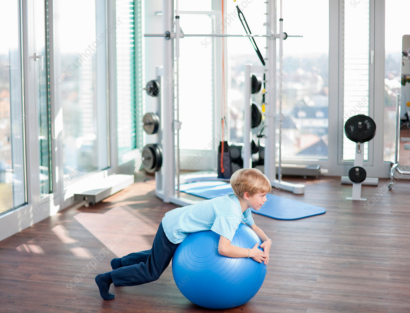 Boy playing with exercise ball in gym