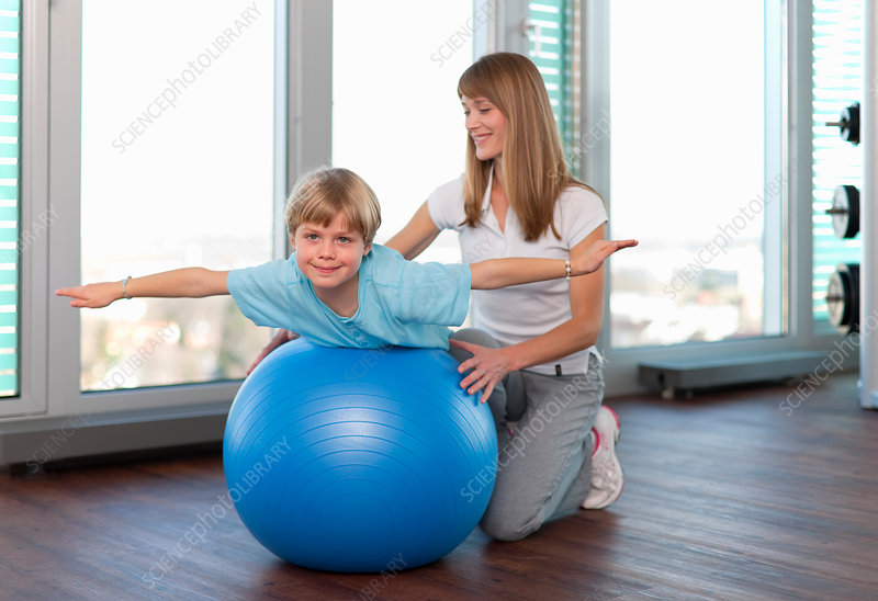 Trainer working with boy in gym