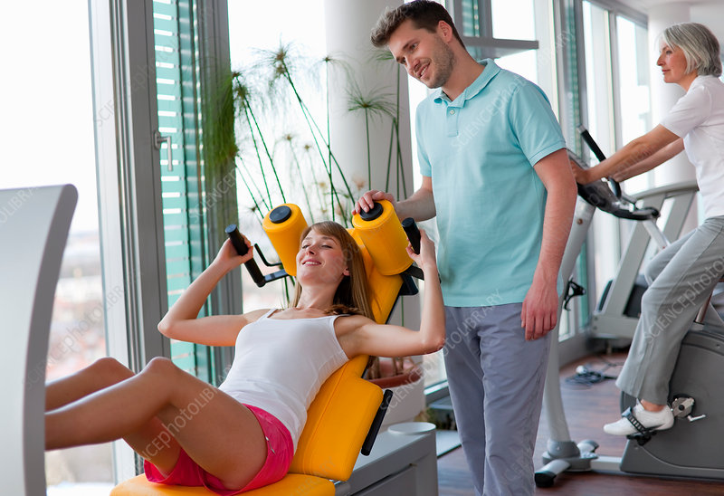 Trainer working with woman in gym
