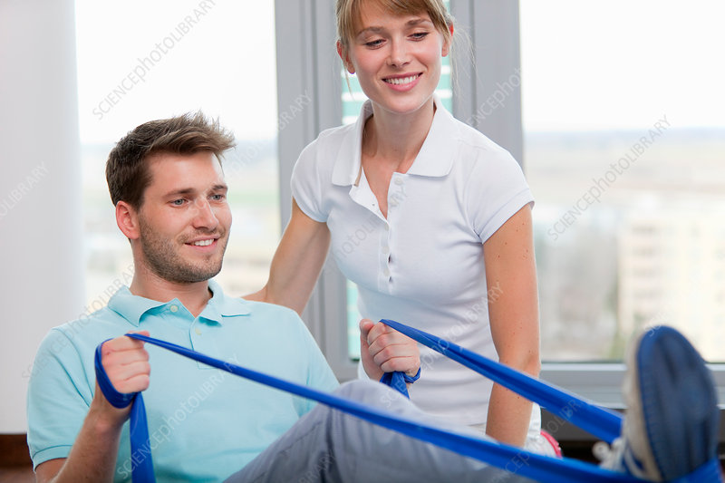 Trainer working with man in gym