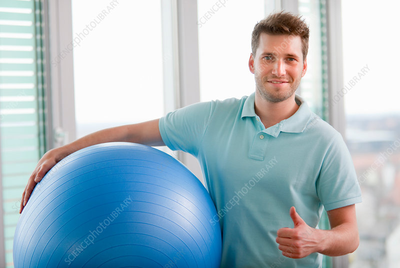 Man carrying exercise ball in gym