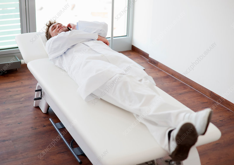 Doctor relaxing on bed in office