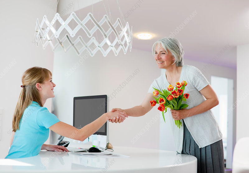 Receptionist shaking woman's hand