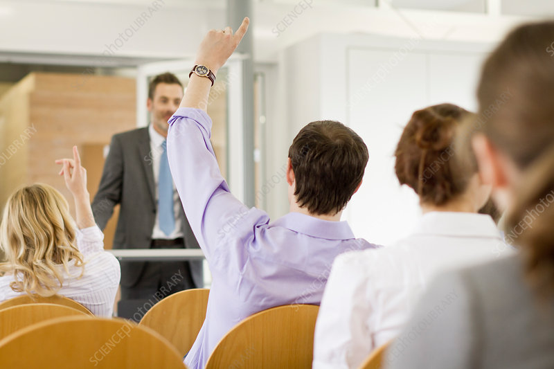Business people raising hands in seminar