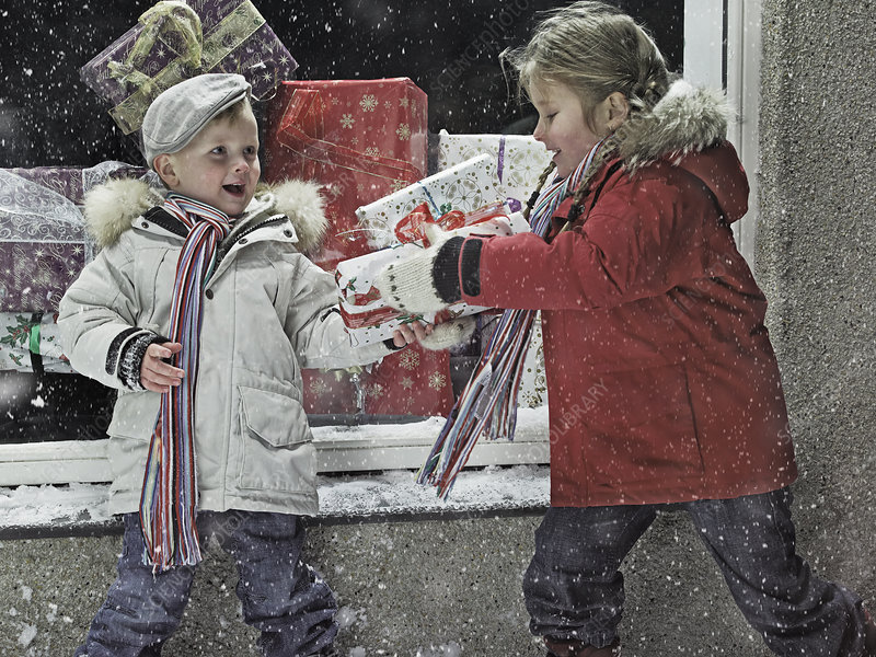Children with Christmas gifts in snow