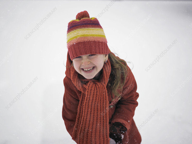 Smiling girl playing in snow